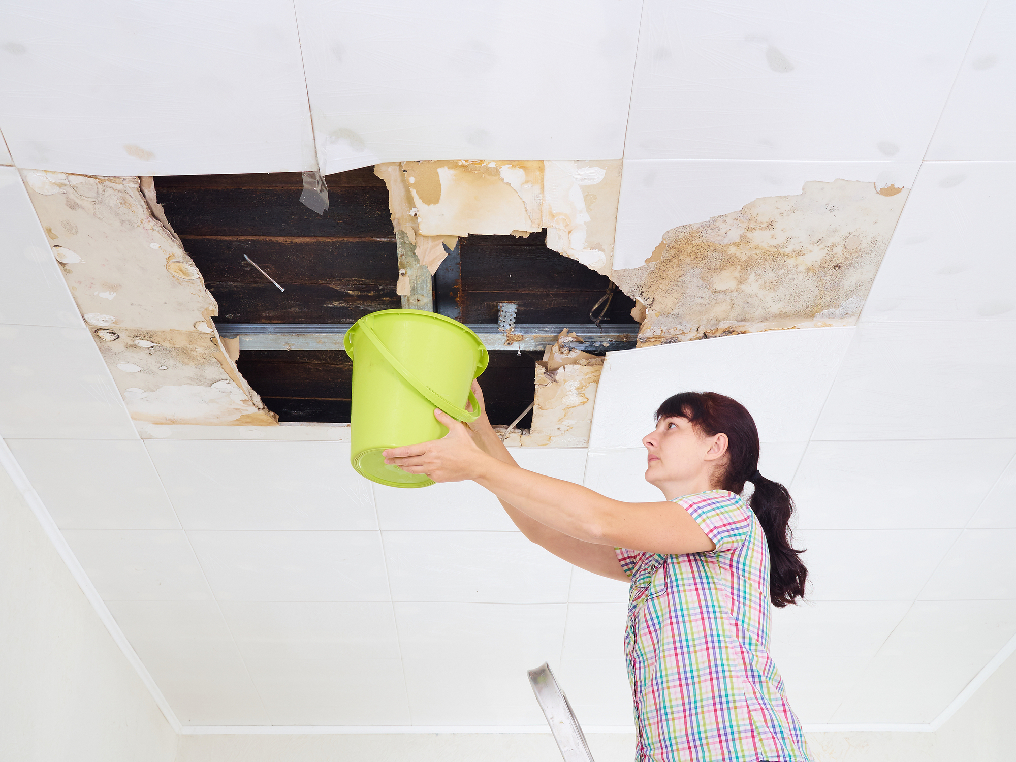 Young woman collecting water from a damaged ceiling